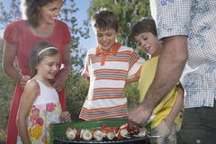 Family Around Grill In Garden - stock photo