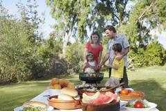 Family At The Grill With Table In Foreground - stock photo