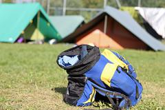 Backpack amid the tents of camp during the adventurous excursion Stock Photos