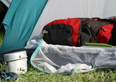 Backpack in the tent and a aluminum lunchbox Stock Photos