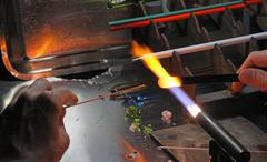 glazier with gas torch lit while blending a piece of glass 5 - stock photo