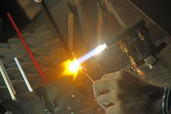 glazier with gas torch lit while blending a piece of glass 1 - stock photo