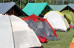 encampment of tents in a soccer field - stock photo