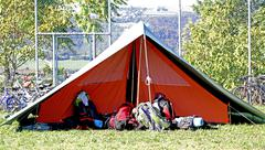 tent of boy scout camp and the rucksack put out in the open air - stock photo