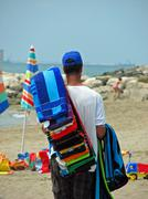 illegal immigrant while sells accessories and towels along the beach - stock photo
