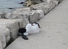 illegal immigrant just landed in the harbor while sleeping on quayside - stock photo