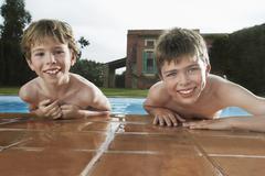 Boys Leaning On Pool's Edge - stock photo
