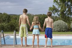 Two Boys And Girl At Pool's Edge - stock photo