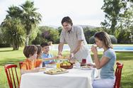 Stock Photo of Family Sitting At Outdoor Breakfast Table