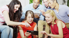 Happy group of friends socializing at home & playing games on a computer tablet Stock Footage