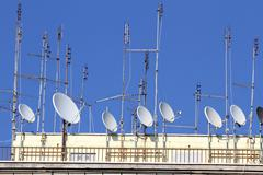 Series of tv antennas and satellite dishes to receive television and radio pr Stock Photos
