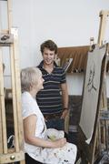 Man Looks At Mature Artist Draw Portrait Stock Photos