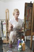 Mature Artist Painting In Art Studio - stock photo