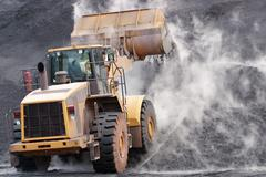 Front loader dumping mineral material on heap Stock Photos