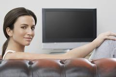 Woman Sitting On Sofa With Flat Screen TV In Background - stock photo