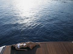 Woman Sunbathing On Yacht's Floorboard By Sea - stock photo
