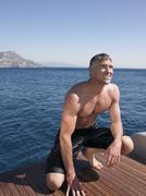 Man Crouching On Yacht's Floorboard - stock photo
