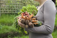 Woman Carrying Freshly Harvested Vegetables - stock photo