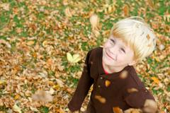 Happy child in falling leaves Stock Photos