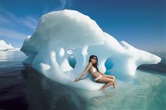 Woman In Bikini Sitting On Iceberg - stock photo