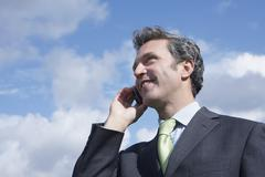 Businessman Using Mobile Phone Against Cloudy Sky - stock photo