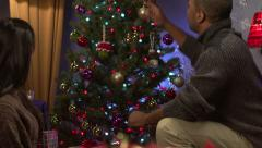 Couple decorating a Christmas tree - Slow Motion - stock footage