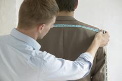 Male Tailor Measuring Customer's Suit Stock Photos