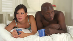 Asian and African American couple drinking coffee Stock Footage