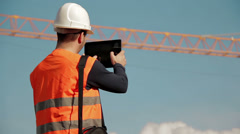 Stock Video Footage of Construction engineer wearing safety vest with yellow crane on the background us