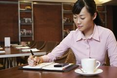 Businesswoman Writing In Diary At Cafe Table Stock Photos