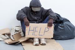 homeless man sitting on a street - stock photo