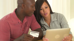 African American and Asian couple making online purchase together - stock footage