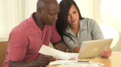 African American and Asian couple paying bills with tablet computer - stock footage