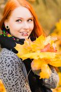 red-haired girl and maple leaf - stock photo