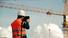 Construction engineer wearing safety vest with yellow crane on the background us Stock Footage