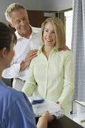 Nurse Handing Examination Gown To Patient - stock photo