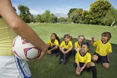 Valmentaja edessä Tyttö Soccer Players Kuvituskuvat
