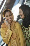 Two Muslim Women One Using cell Phone - stock photo