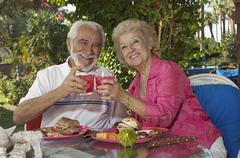 Stock Photo of Senior Couple Toasting Glasses Of Drinks