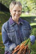 Woman Holding Bunch Of Muddy Carrots - stock photo