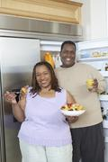 Couple With Food And Drink By Open Fridge Stock Photos