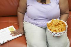 Obese Woman With A Bowl Of Nachos - stock photo