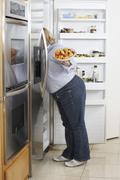 Woman Looking Into Fridge - stock photo