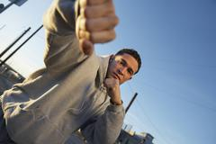 Boxer In Sweatshirt Punching Against Sky Stock Photos