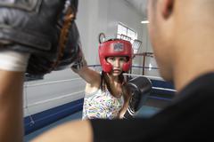 Female Boxer Striking Her Target In Ring Stock Photos