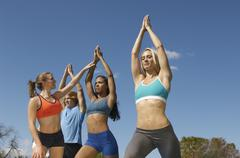 Group Exercising With Instructor In Park Stock Photos