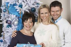Young Couple Giving Christmas Present To Woman - stock photo