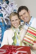 Couple Standing Together With Christmas Gifts - stock photo