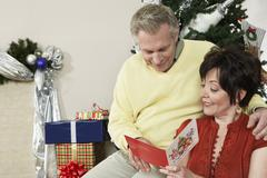Couple Reading Greeting Card With Christmas Gifts Besides - stock photo