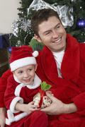 Father And Son In Santa Claus Outfit Holding Present - stock photo